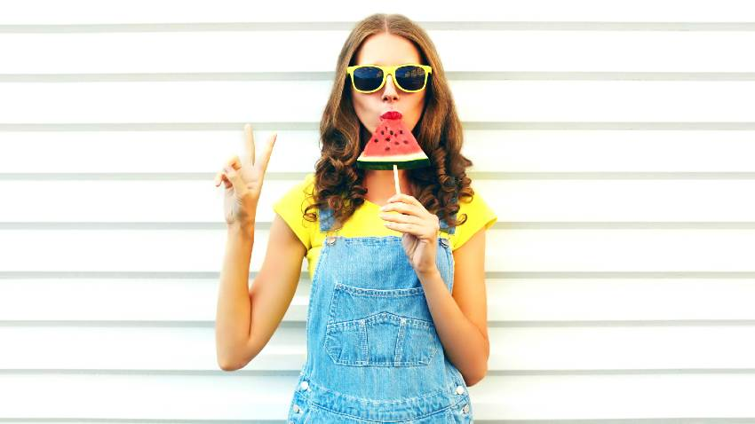Fashion cool girl eating a slice of watermelon in the form of ice cream on a white background